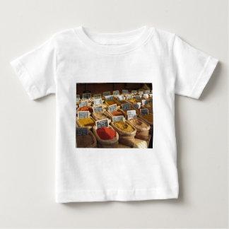 As especiarias coloridas na juta ensacam no camiseta para bebê