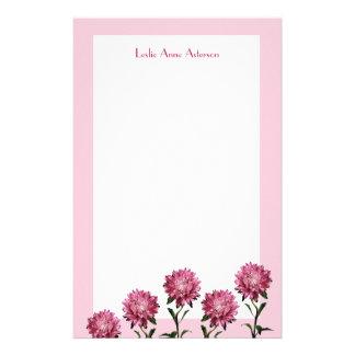 Ásteres cor-de-rosa com papel de nota da beira papelaria