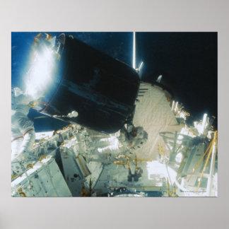 Astronautas que reparam um satélite no espaço poster