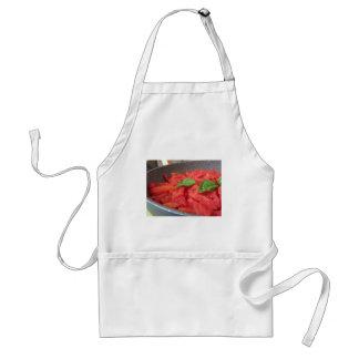 Avental Cozinhando o molho de tomate caseiro usando o