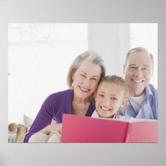 Avós de sorriso que lêem o livro de receitas com poster