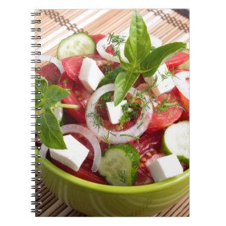 Bacia verde com o vegetariano saboroso e integral cadernos