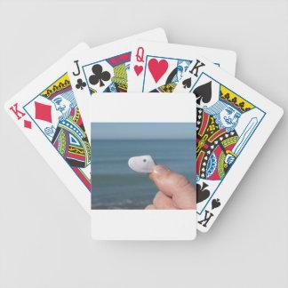 Baralho Guardarando um seashell na mão com mar azul