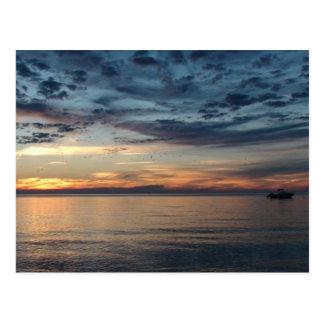 Barco no por do sol no cartão do oceano
