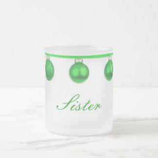 Baubles verdes na caneca do Natal da irmã da fita