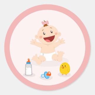 Bebé em etiquetas cor-de-rosa do chá de fraldas do