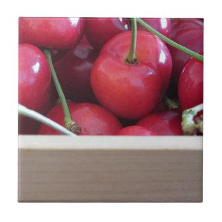 Beira de cerejas frescas no fundo de madeira