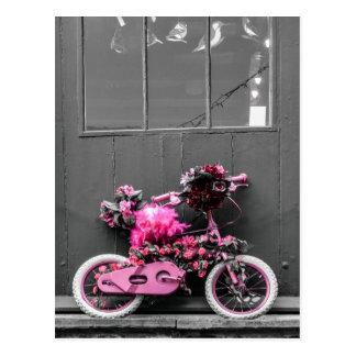 Bicicleta cor-de-rosa com flores e as penas cor-de cartoes postais