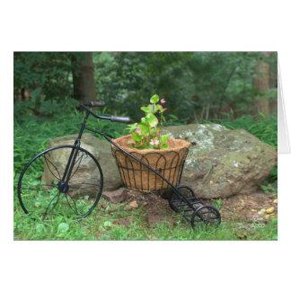 Bicicleta do cartão vazio com as flores cor-de-ros