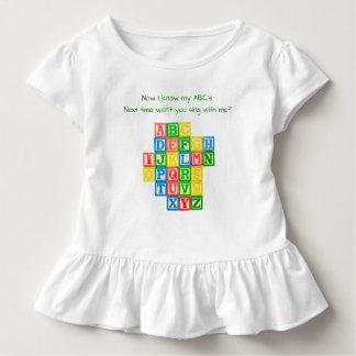 Blocos do alfabeto no vestido de uma criança