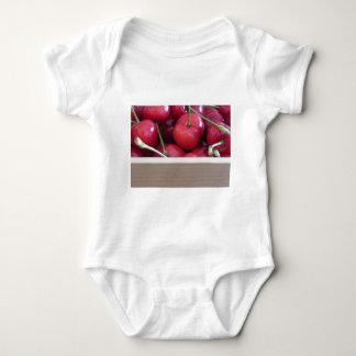 Body Para Bebê Beira de cerejas frescas no fundo de madeira