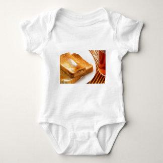 Body Para Bebê Brinde quente com manteiga em uma placa branca