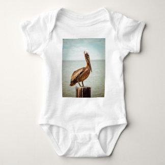 Body Para Bebê Pelicano bonito empoleirado sobre o oceano