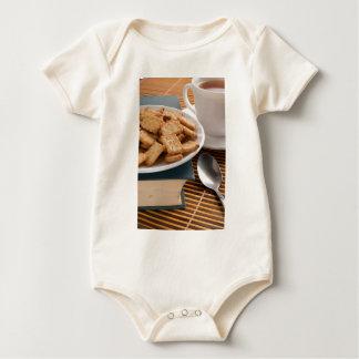 Body Para Bebê Placa branca com os biscoitos no livro velho