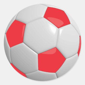 Bola de futebol vermelha e branca do esporte adesivo