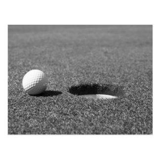 Bola de golfe ao lado do furo cartão postal
