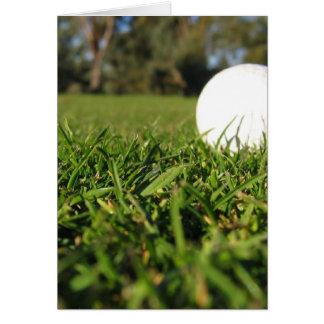 Bola de golfe no cartão do campo de golfe
