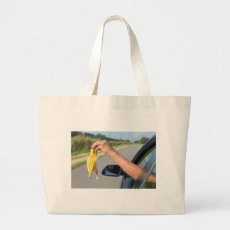 Bolsa Tote Grande Casca deixando cair do braço da janela de carro da