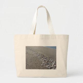 Bolsa Tote Grande Seashells na areia. Fundo da praia do verão