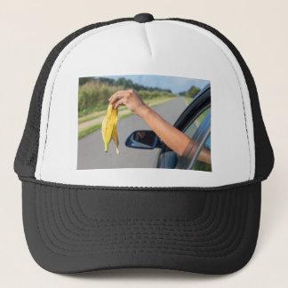 Boné Casca deixando cair do braço da janela de carro da