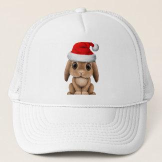 Boné Coelho do bebê que veste um chapéu do papai noel