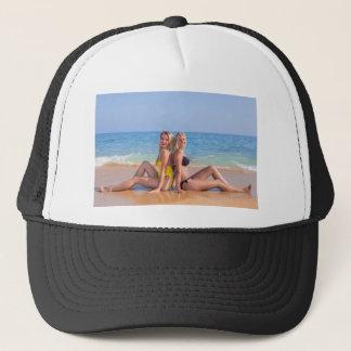 Boné Duas meninas sentam-se na praia perto de sea.JPG