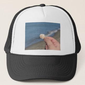Boné Guardarando um seashell na mão
