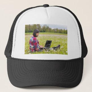 Boné Mulher que senta-se com o laptop no prado do