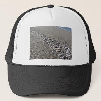 Boné Seashells na areia. Fundo da praia do verão