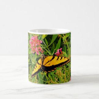 Borboleta de monarca no copo de café cor-de-rosa caneca de café