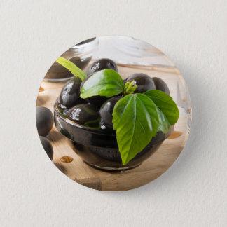Bóton Redondo 5.08cm Azeitonas pretas em uma mesa e em copos do vidro