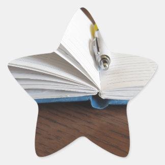 Caderno alinhado vazio aberto com caneta adesito estrela