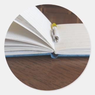 Caderno alinhado vazio aberto com caneta adesivo