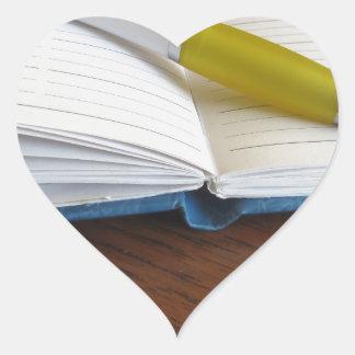 Caderno alinhado vazio aberto com caneta adesivo coração