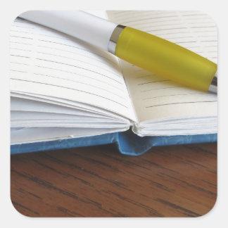 Caderno alinhado vazio aberto com caneta adesivo quadrado