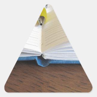 Caderno alinhado vazio aberto com caneta adesivo triangular