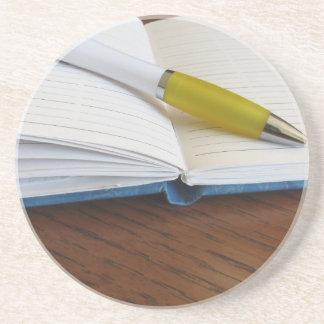 Caderno alinhado vazio aberto com caneta porta copos de arenito