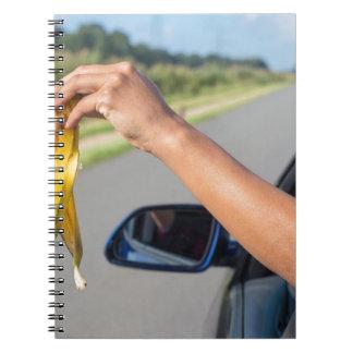 Caderno Casca deixando cair do braço da janela de carro da