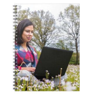 Caderno Espiral A mulher senta-se com o laptop no prado de