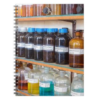 Caderno Espiral Fileiras dos produtos químicos fluidos em umas