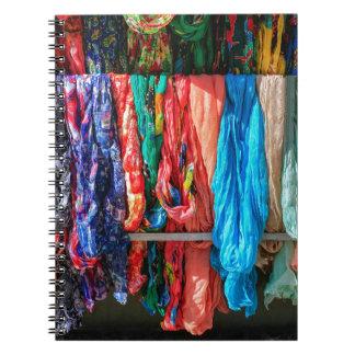 Caderno Espiral Muitos scarves coloridos que penduram no mercado