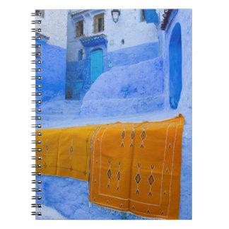 Caderno Espiral Tapetes drapejados em uma parede azul