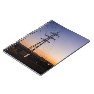 Caderno Espiral Torre da eletricidade perto de uma área urbana