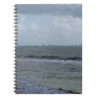 Caderno Litoral da praia com os veleiros no horizonte