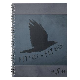 Caderno Um corvo em vôo no fundo azul & cinzento sujo