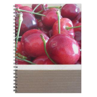Cadernos Beira de cerejas frescas no fundo de madeira