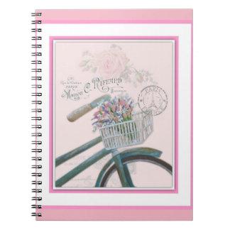 Cadernos Bicicleta com as flores no fundo cor-de-rosa