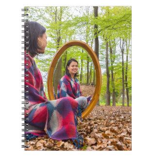 Cadernos Espiral A mulher senta-se com o espelho na floresta