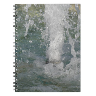 Cadernos Espirra da água da fonte em um dia ensolarado