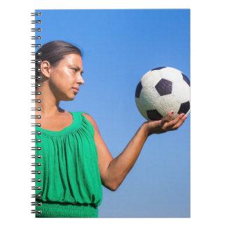 Cadernos Jovem mulher que guardara o futebol na mão com céu